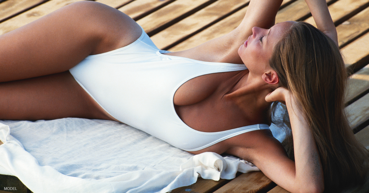 voluptuous woman in white one piece lying on her side